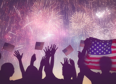 People holding American Flags while watching fireworks