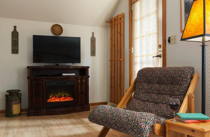 Matterhorn Suite living room with chair, fireplace, and TV at our Amish Country B&B