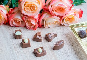 Pink roses and chocolates on a table