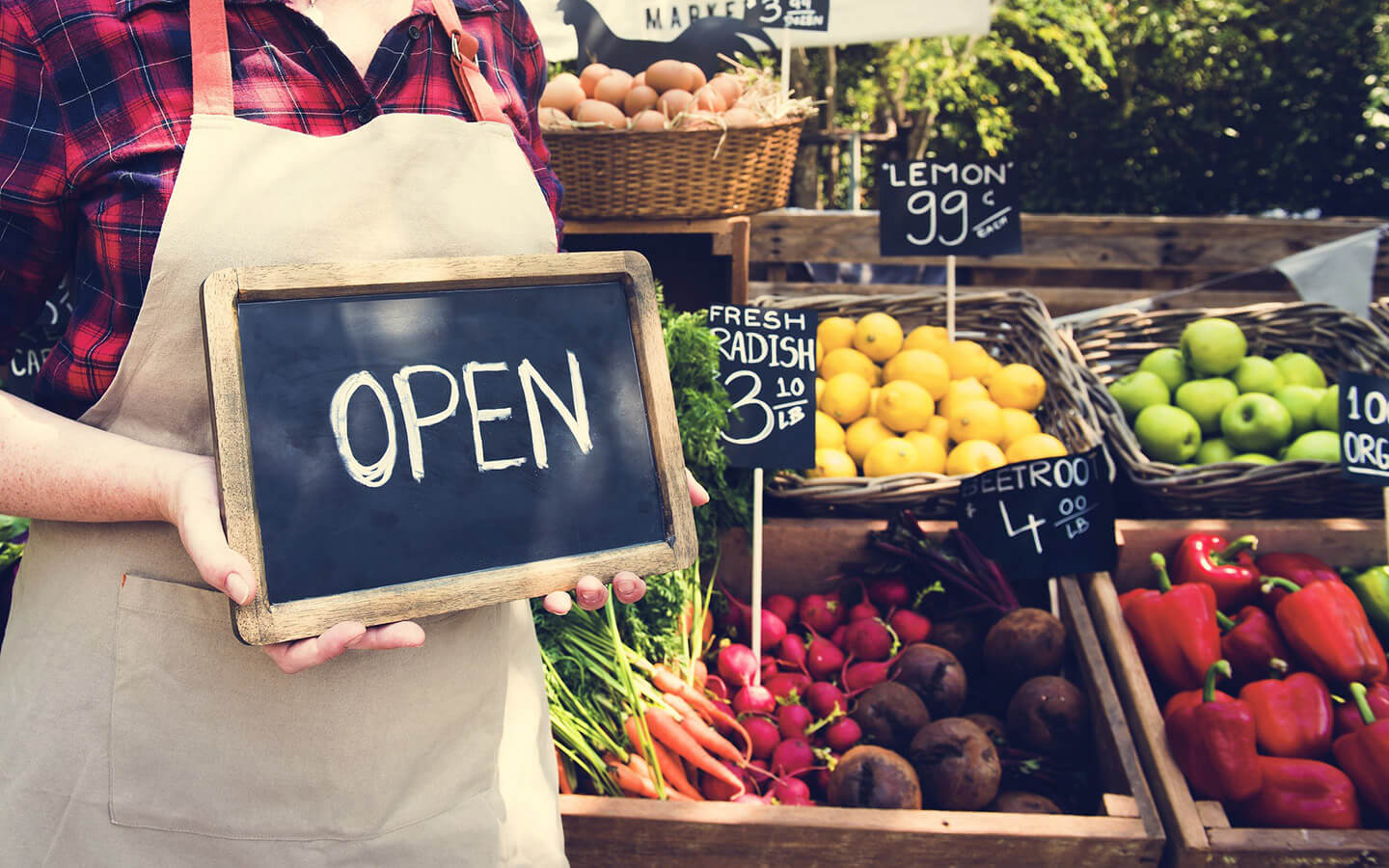 Farmers market with person holding an 'Open' sign