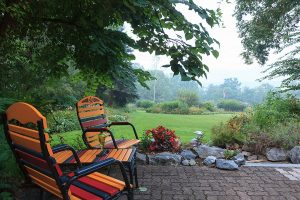 Colorful chairs on the patio with view of garden at our Amish Country B&B