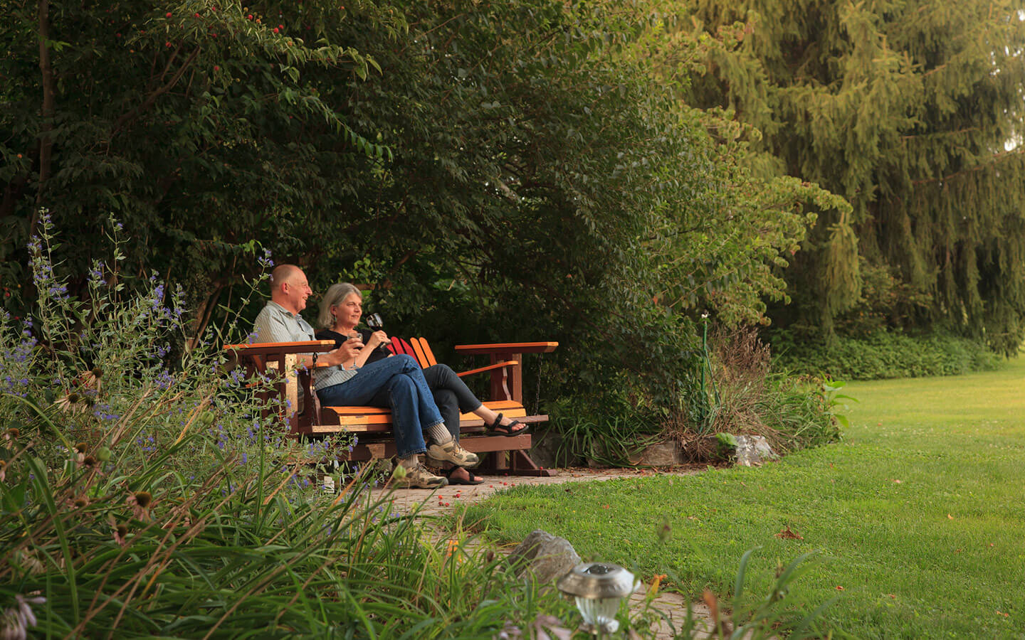Couple drinking wine on a bench in the gardens at our Lancaster County B&B